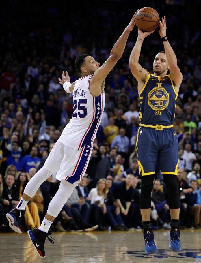 Philadelphia 76ers' Ben Simmons, left, defends against Golden State Warriors' Stephen Curry (30) during the second half of an NBA basketball game Thursday, Jan. 31, 2019, in Oakland, Calif. (AP Photo/Ben Margot)
