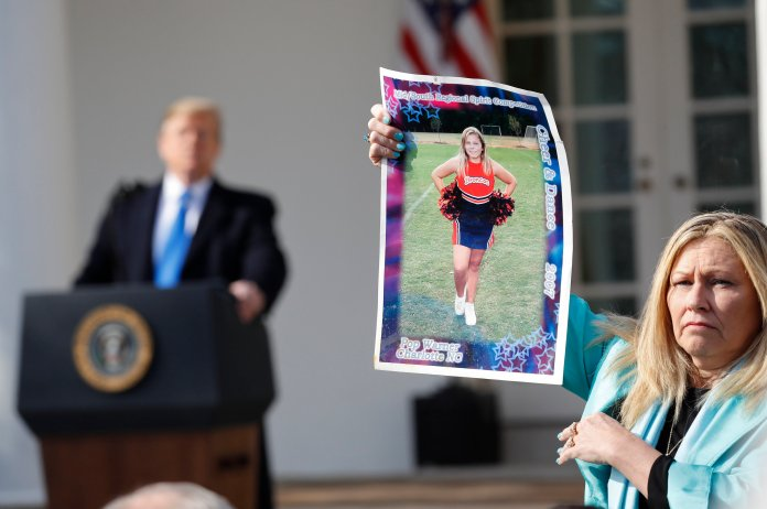 President Donald Trump, left, looks over to Susan Stevens, right, who is holding up a picture of her daughter, during an event in the Rose Garden at the White House to declare a national emergency in order to build a wall along the southern border, Friday, Feb. 15, 2019 in Washington. Stevens lost her daughter to opioids. (AP Photo/Pablo Martinez Monsivais)