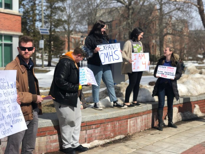 Students wielding posters and signs gathered at the University of Connecticut Great Seal Wednesday demanding better mental health care from the university and Counseling and Mental Health Services. (Naiela Suleiman/The Daily Campus)