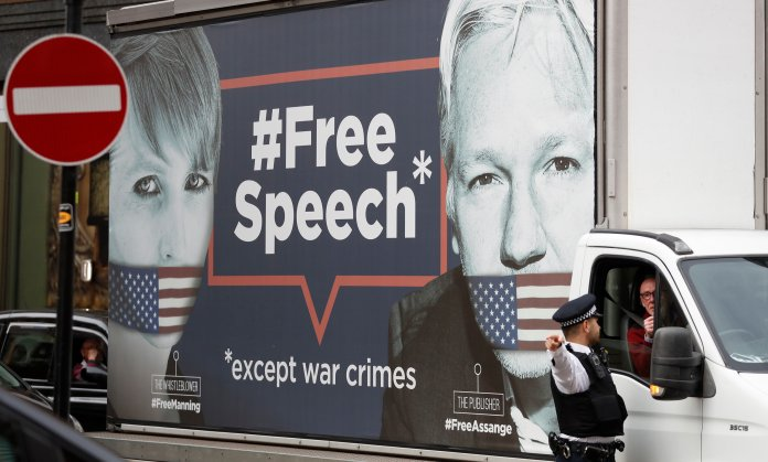 """A policeman directs a van with a 'Free Speech' placard and the images of Wikileaks founder Julian Assange and whistleblower Chelsea Manning on its side, near the Ecuadorian Embassy, in London, Friday, April 5, 2019. Assange has been hold out since in the embassy since 2012. A senior Ecuadorian official said no decision has been made to expel Julian Assange from the country's London embassy despite tweets from Wikileaks that sources had told it he could be kicked out within """"hours to days"""" on Friday. (AP Photo/Alastair Grant)"""