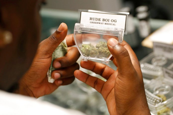 FILE - In this April 20, 2018, file photo, a customer shops for marijuana at the Exhale Nevada dispensary in Las Vegas. Complaints that the state releases no information about who applies for and receives dispensary licenses in Nevada's booming retail marijuana business are spurring lawsuits and legislative proposals that appear poised to push the process public. (AP Photo/John Locher, File)