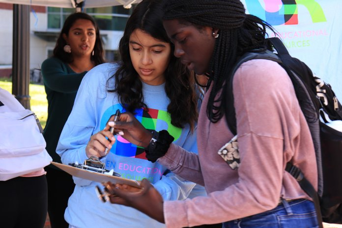 Members of PIRG hand out T-shirts on Fairfield way. Students who passed by their table were asked to complete a survey about how much they paid for textbooks this year.  Photo by Erin Knapp/The Daily Campus