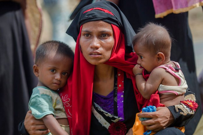 Rohingya Muslim woman, Rukaya Begum, who crossed over from Myanmar into Bangladesh, holds her son Mahbubur Rehman, left and her daughter Rehana Bibi, after the government moved them to newly allocated refugee camp areas, near Kutupalong, Bangladesh.  Photo by Dar Yasin/AP