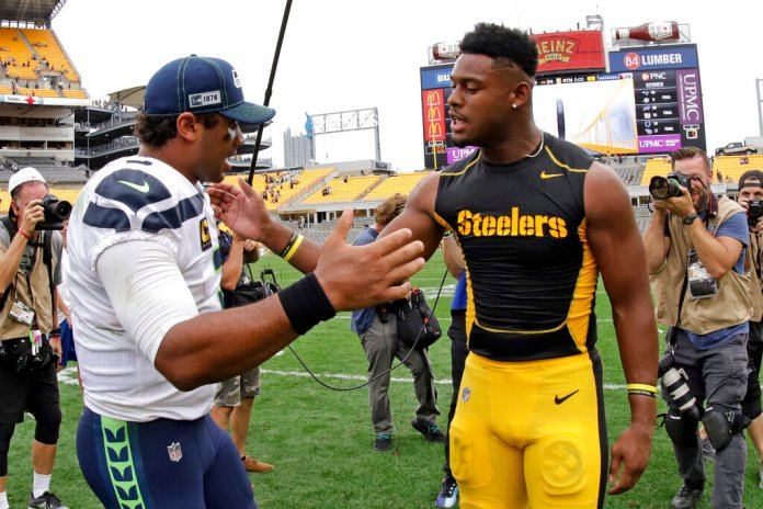 Seattle Seahawks quarterback Russell Wilson, left, greets Pittsburgh Steelers wide receiver JuJu Smith-Schuster after an NFL football game.   Photo by Gene J. Puskar/AP