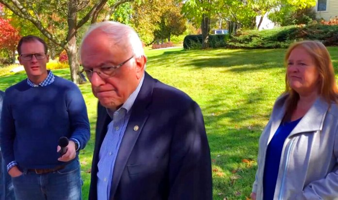 """In this image taken from video, Democratic presidential candidate Sen. Bernie Sanders, I-Vt., speaks we reporters outside his home, Tuesday, Oct. 8, 2019, in Burlington, Vt. His wife, Jane O'Meara Sanders listens at right. Sanders says he was """"dumb"""" not to have listened to the symptoms he was experiencing before he was stricken with a heart attack last week.  Photo courtesy of AP Photo/Wilson Ring. Thumbnail photo courtesy of AP Photo/Jose Luis Magana."""