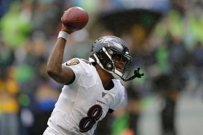 Baltimore Ravens quarterback Lamar Jackson (8) spikes the ball after a touchdown during the second half of an NFL football game against the Seattle Seahawks.  Photo by John Froschauer/AP