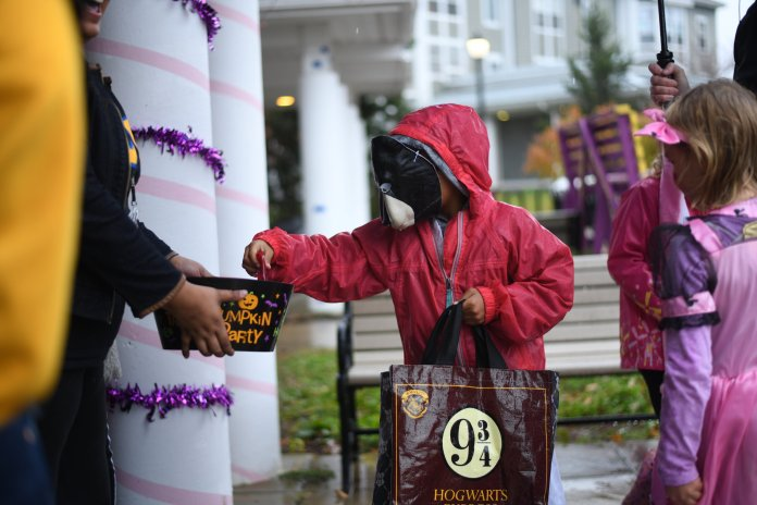 The Center for Fraternity and Sorority Development hosts Fall Fest this Sunday at Husky Village. Even in the pouring rain, kids came to the houses for trick-or-treating.  Photos by Charlotte Lao / The Daily Campus.