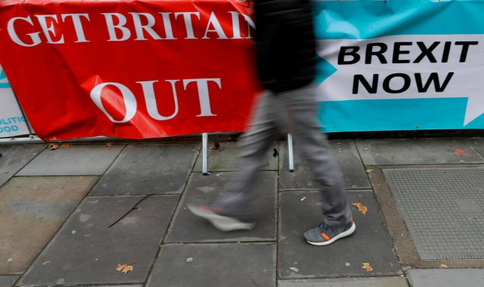 A pedestrian walks past Brexit banners outside Parliament in London, Friday, Oct. 25, 2019. Politicians in Britain and the European Union seem to be looking to each other to break the Brexit deadlock.  Photo by Kirsty Wigglesworth/AP