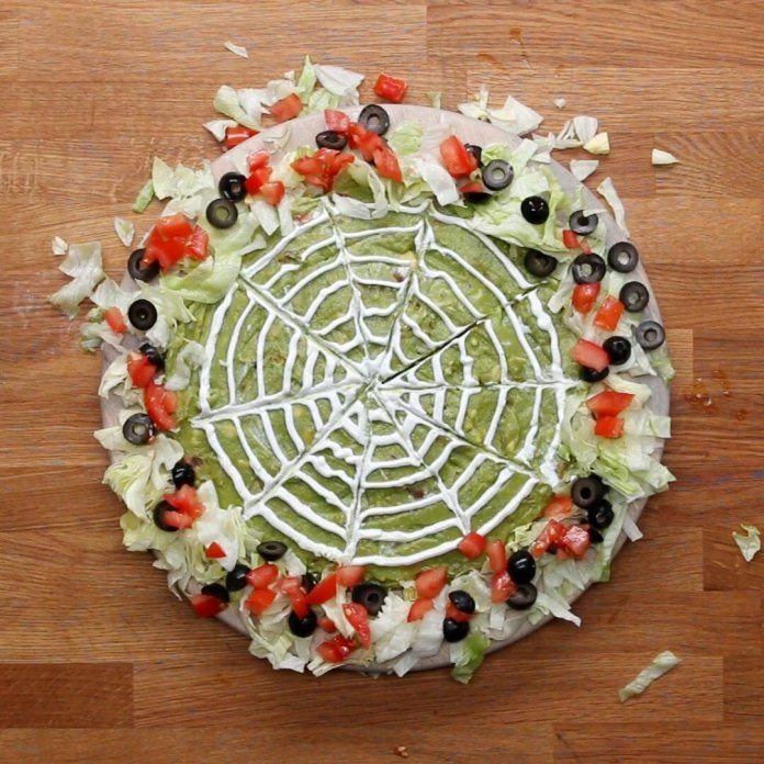 Halloween layered dip consists of beans, salsa, guacamole, and is perfect for a Halloween party.  Photo courtesy of    Tasty
