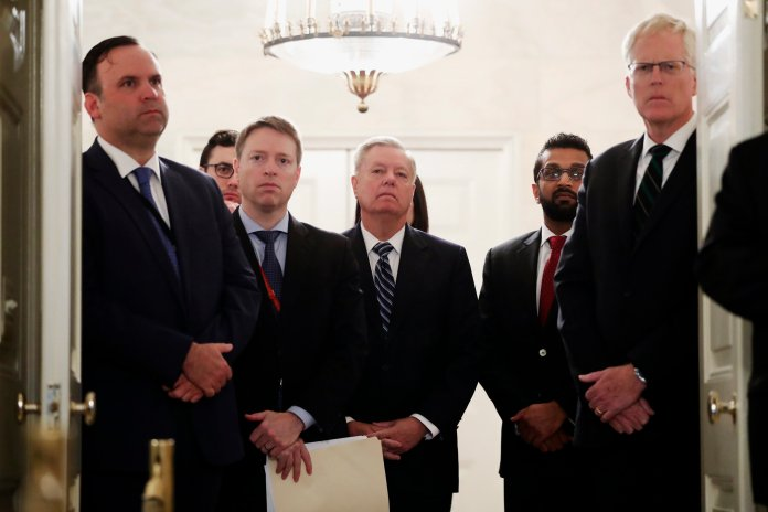 Sen. Lindsey Graham, R-S.C., center, listens as President Donald Trump speaks in the Diplomatic Room of the White House in Washington, Sunday, Oct. 27, 2019, to announce that Islamic State group leader Abu Bakr al-Baghdadi has been killed during a U.S. raid in Syria.  AP Photo/Andrew Harnik