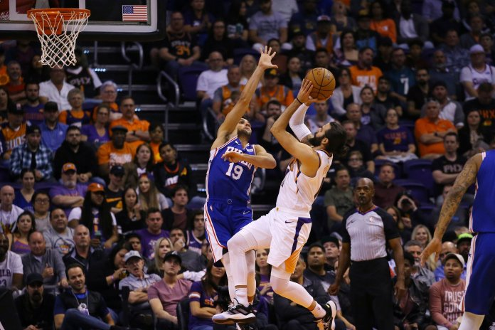 Phoenix Suns guard Ricky Rubio, center right, shoots over Philadelphia 76ers guard Raul Neto (19) during the first half of an NBA basketball game Monday, Nov. 4, 2019, in Phoenix. Phoenix has opened the season at 5-2, and after their most recent win against the then-unbeaten 76ers, are starting to garner some attention in the league. (AP Photo/Ross D. Franklin)