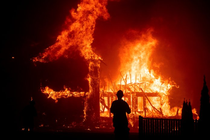In this Nov. 8, 2018, file photo, a home burns during a wildfire in Paradise, Calif.  In 2018 , the devastation left by these wildfires amounted to $11.8 billion in insurance payouts, not even including the nearly $3 billion of debris clean up, nearly three times the cost of debris clean up when compared to the previous year.  Photo courtesy of the Associated Press.