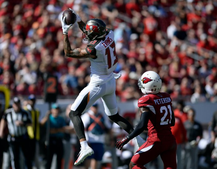 Tampa Bay Buccaneers wide receiver Mike Evans (13) makes a leaping catch in front of Arizona Cardinals cornerback Patrick Peterson (21) during the first half of an NFL football game Sunday, Nov. 10, 2019, in Tampa, Fla. (AP Photo/Jason Behnken)