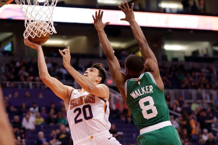 Phoenix Suns forward Dario Saric (20) shoots around Boston Celtics guard Kemba Walker (8) during the second half of an NBA basketball game, Monday, Nov. 18, 2019, in Phoenix. (AP Photo/Matt York)