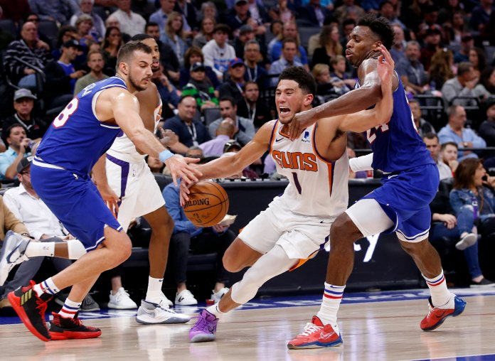 Phoenix Suns guard Devin Booker, center, is fouled by Sacramento Kings guard Buddy Hield, right, during the second half of an NBA basketball game in Sacramento, Calif., Tuesday, Nov. 19, 2019. At left is Kings forward Nemanja Bjelica. (AP Photo/Rich Pedroncelli)