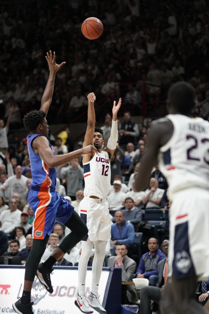 Tyler Polley (12) shoots the ball. The Huskies will play the Iona Gaels Wednesday at Gampel Pavilion 7 p.m.  Photo by Maggie Chafouleas/The Daily Campus