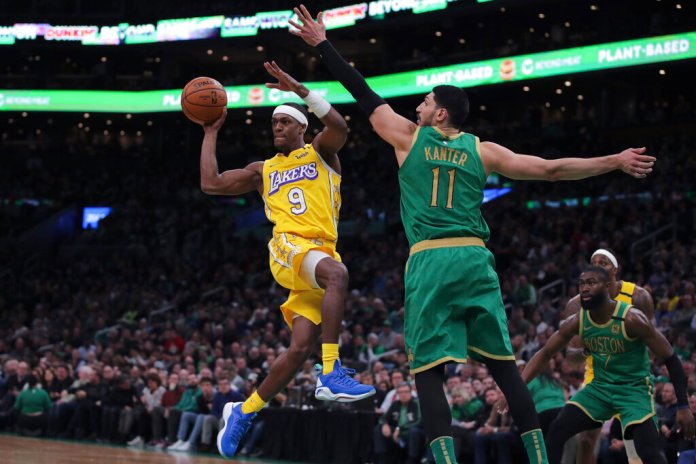 Los Angeles Lakers guard Rajon Rondo (9) passes the ball as he is pressured by Boston Celtics center Enes Kanter (11) during the fourth quarter of an NBA basketball game in Boston.  Photo courtesy of Charles Krupa/AP Photo