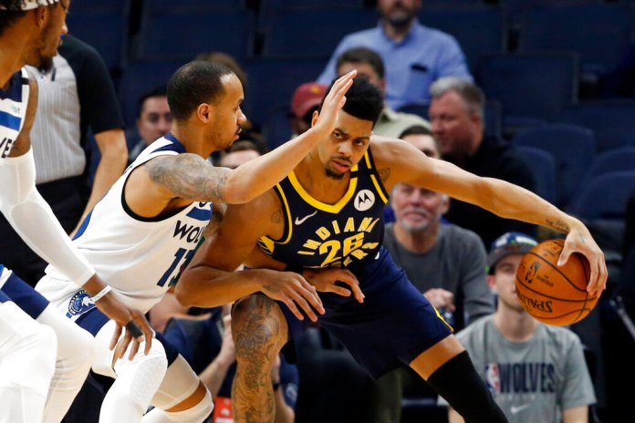 Indiana Pacers' Jeremy Lamb, right, tries to work around Minnesota Timberwolves' Shabazz Napier in the first half of an NBA basketball game Wednesday.  Photo courtesy of Jim Mone/AP Photo
