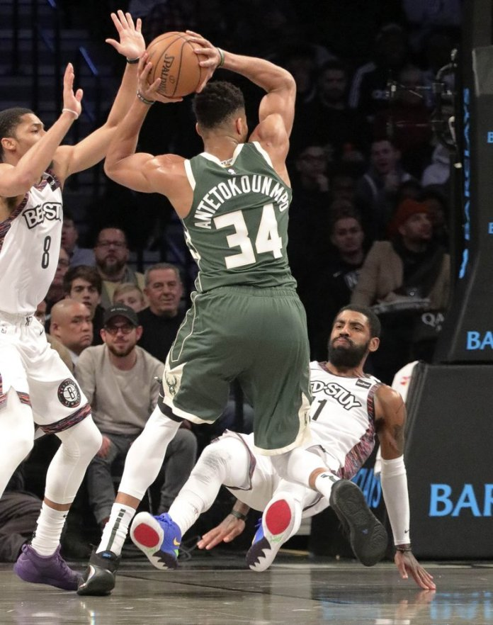Brooklyn Nets guard Kyrie Irving, right, goes to the ground as Milwaukee Bucks forward Giannis Antetokounmpo gets an offensive foul driving to the basket, during an NBA basketball game, Saturday in New York.  Photo courtesy of Bebeto Matthews/AP Photo