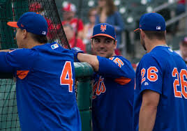 Mets players Wilmer Flores (L), Matt Reynolds (center), and Kevin Plawecki (R) hanging out at the batting cage before the Mets vs. Cardinals Spring Training game, 2017.  Photo in the    public domain