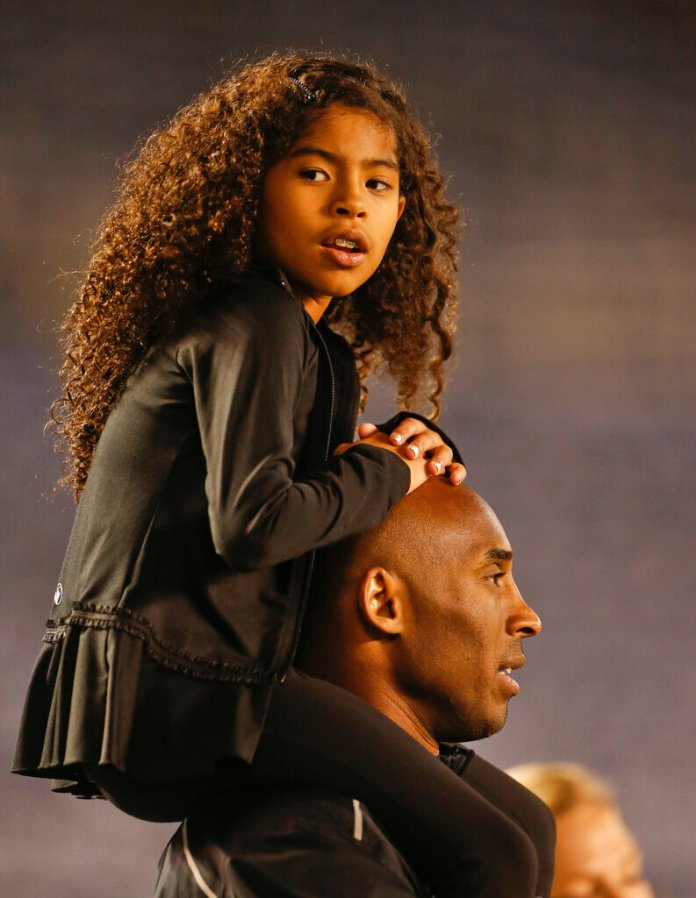 Gianna Maria-Onore Bryant sits on the shoulders of her father, Kobe, as they attend the women's soccer match between the United States and China Thursday, April 10, 2014, in San Diego.   Photo by Lenny Ignelzi/AP