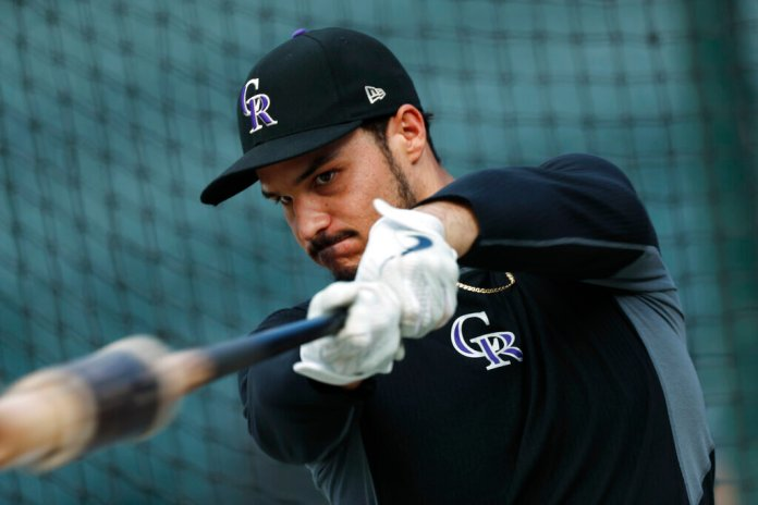 Colorado Rockies third baseman Nolan Arenado warms up before a baseball game against the Milwaukee Brewers in Denver. There has been consistent controversy surrounding the superstar, who has voiced his discomfort with the team's front office following offseason-wide trade rumors.  Photo courtesy of David Zalubowski/AP Photo