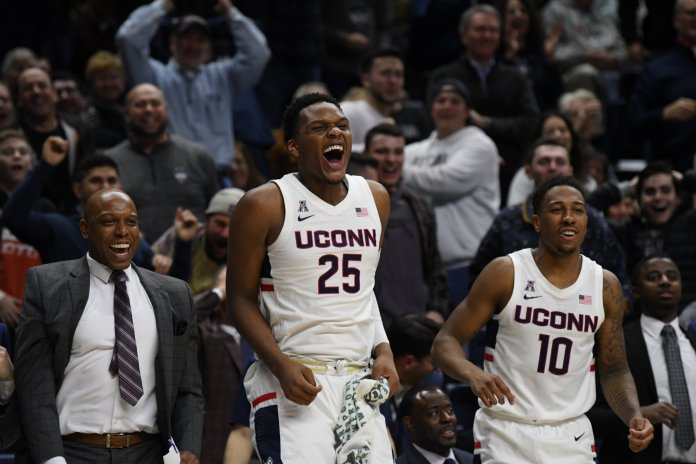 The UConn men's basketball team beat the Temple Owls 78-63 in a conference, earning just their second conference win this season. Starting center, Josh Carlton, and sophomore Brendan Adams celebrate on the bench during the game.  Photo by Brandon Barzola, Grabs Photographer/The Daily Campus