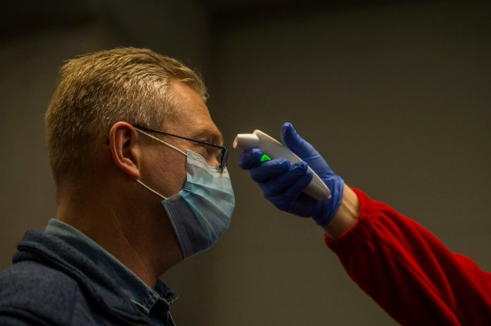 The temperature of a person is checked as precautionary measures against the spreading of novel coronavirus, at Budapest Liszt Ferenc International Airport in Budapest, Hungary. (Zoltan Balogh/MTI via AP)