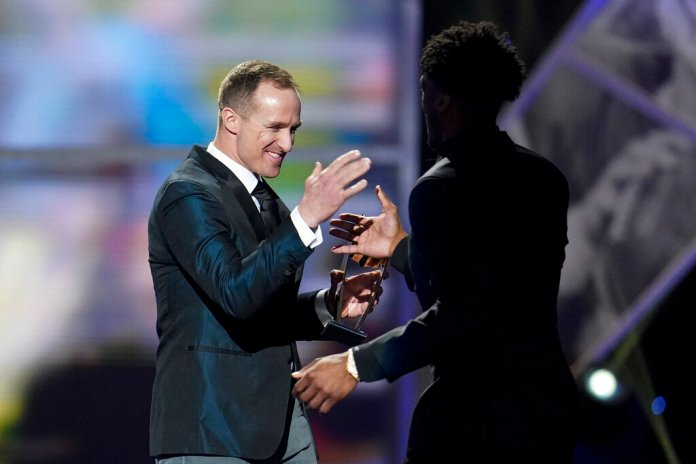 New Orleans Saints quarterback Drew Brees gives Saints' Michael Thomas his AP Offensive Player of the Year award at the NFL Honors football award show Saturday, Feb. 1, 2020, in Miami. Photo courtesy of David J. Phillip/AP