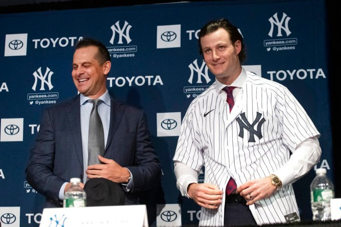"""New York Yankees manager Aaron Boone, left, smiles as Gerrit Cole tries on a Yankee jersey as he is introduced in New York. The pitcher agreed to a 9-year $324 million contract. """"He's going to be a game changer for us,"""" Yankees owner Hal Steinbrenner said. """"The city's buzzing, and it's continued since the day we signed him.""""  Photo courtesy of Mark Lennihan/AP"""