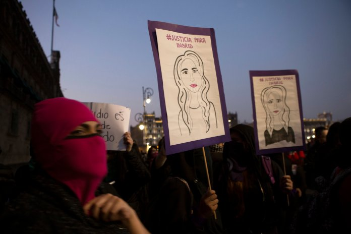 Masked, female protesters hold drawings resembling Ingrid Escamilla, who was killed by her boyfriend last week, during a protest against gender violence outside the National Palace, the presidential office and residence, in Mexico City, Friday, Feb. 14, 2020. The demonstration against gender violence comes after Escamilla's vicious murder and controversy unleashed by the leaking of images of her body to the press, in a country where an average of 10 women are killed every day.  Photo courtesy of Ginnette Riquelme / AP Photo.