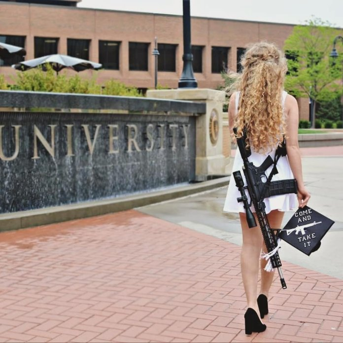 The famous photo from Kaitlin Bennett's graduation photoset. Last Tuesday Kaitlin Bennett visited Ohio University and was met with riots.  @kait.meow