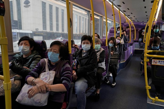 Passengers wears face masks as a precaution against the COVID-19 while sitting in a bus in Hong Kong, Thursday, Feb. 27, 2020. Photo by Kin Cheung / AP Photo