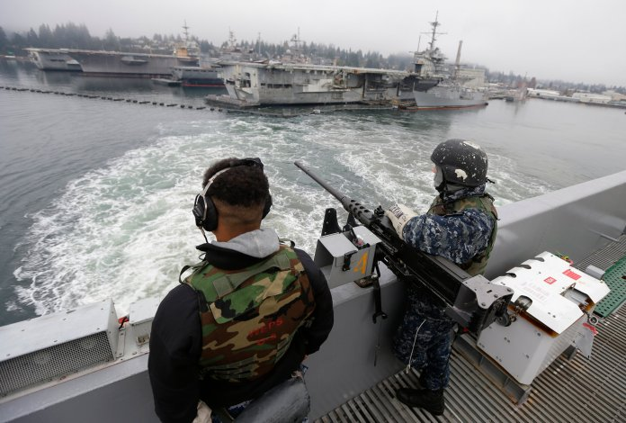 In this Jan. 13, 2015, file photo, two sailors stand with a gun as the USS John Stennis aircraft carrier leaves Naval Base Kitsap in Washington state. A federal judge in Seattle ruled Thursday, Feb. 27, 2020, that President Donald Trump cannot divert $89 million intended for a construction project at the base to help build his wall on the U.S.-Mexico border.  Photo by Ted S. Warren / AP Photo.