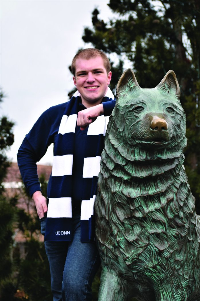 A photo of Damon Reynolds next to the Jonathon the Husky statue. Damon Reynolds is one of two candidates for the student seat on the Board of Trustees.  Photo Courtesy of Damon Reynolds