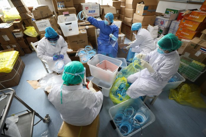 Nurses assemble plastic face shields at a hospital designated for the coronavirus patients in Wuhan in central China's Hubei province, Sunday, March 1, 2020. New York confirmed Sunday the state's first positive test of the new virus that has sickened tens of thousands of people across the globe.  (Chinatopix via AP)