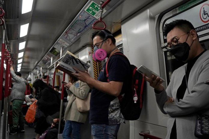 People wear masks on a subway train in Hong Kong, Tuesday, March 3, 2020. Officials in Hong Kong have taken theCOVID-19epidemic as an opportunity to quash the pro-democracy protests that have been simmering for months.  Photo courtesy of Kin Cheung / AP Photo.