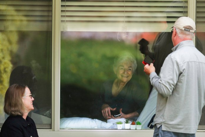 Judie Shape, center, who has tested positive for the new coronavirus, but isn't showing symptoms, smiles as she visits through the window and on the phone with her daughter Lori Spencer, left, and her son-in-law Michael Spencer, Tuesday, March 17, 2020, at the Life Care Center in Kirkland, Wash., near Seattle. In-person visits are not allowed at the nursing home, which is at the center of the outbreak of the new coronavirus in the United States.  Photo by Ted S. Warren/AP