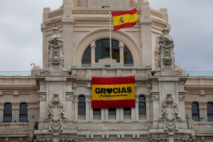 """A sign that reads in spanish: """"Thank you #IstayAtHome"""" hangs on the facade of the Madrid city hall, Spain, on Sunday March 22, 2020. For most people, the new coronavirus causes only mild or moderate symptoms. For some it can cause a more serious illness.  Photo by Bernat Armangue/AP"""