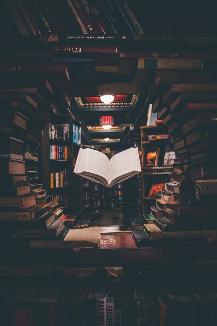 A photo of a floating book surrounded by bookshelves. Picking up a new book is a great way to pass the time during quarantine.  Photo by    Jaredd Craig    on    Unsplash