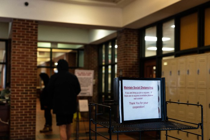 A sign in the line for pick up meals in South Dining Hall reminds students to remain distant from one another while waiting to enter.  Photo by Maggie Chafouleas/The Daily Campus
