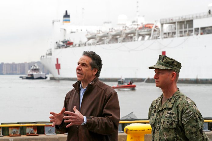 New York Go. Andrew Cuomo, left, speaks as he stands beside Rear Adm. John B. Mustin after the arrival of the USNS Comfort, a naval hospital ship with a 1,000 bed-capacity at Pier 90 in New York. The ship will be used to treat New Yorkers who don't have coronavirus as land-based hospitals fill up with and treat those who do.  Photo by Kathy Willens/AP