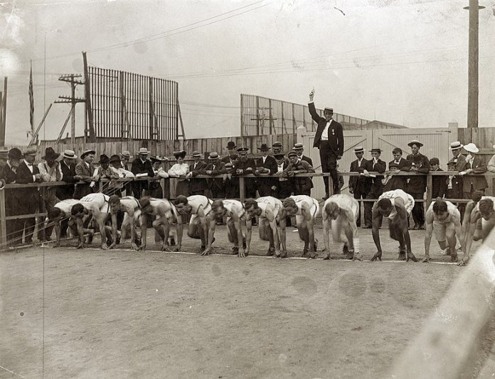 Twelve athletics in starting position of the 400 meter race in the 1904 Olympics. Photo in the  public domain