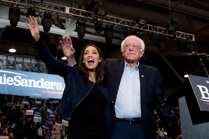 "Democratic presidential candidate Sen. Bernie Sanders, accompanied by Rep. Alexandria Ocasio-Cortez, takes the stage at campaign stop at the University of New Hampshire in Durham, N.H. Choosing a presidential candidate based primarily on loathing the alternative is not the strongest of electoral strategies. That's why leaders of the progressive movement say many Americans who were enthralled by Bernie Sanders and his slogan of ""Not Me. Us,"" won't be as likely to settle for Joe Biden. Photo courtesy of Andrew Harnik / AP Photo."