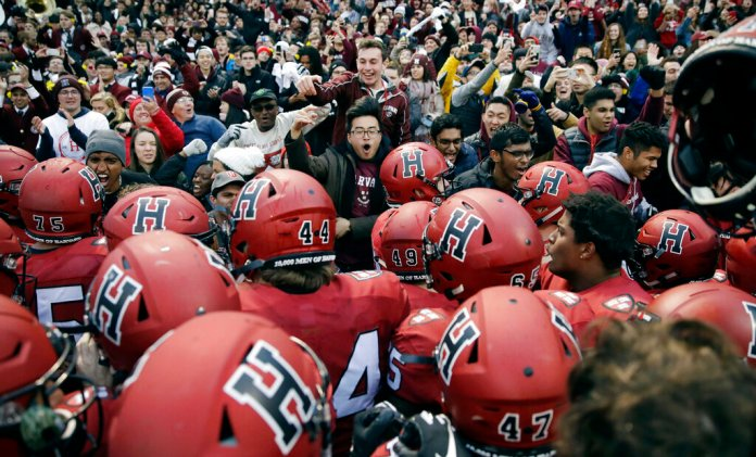 In this Nov. 17, 2018, file photo, Harvard players, students and fans celebrate their 45-27 win over Yale after an NCAA college football game at Fenway Park in Boston. The Ivy League has canceled all fall sports because of the coronavirus pandemic.  Photo by Charles Krupa/AP File