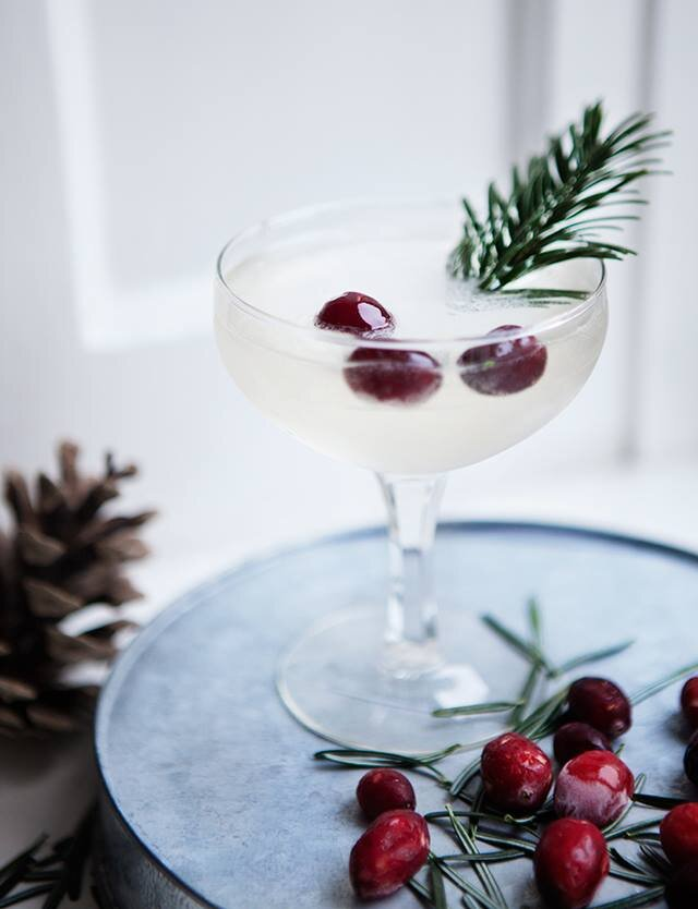 Cranberry Rosemary Champagne Cocktail - This cocktail is highly adaptable as you can serve it with champagne, Prosecco, or for a non-alcoholic version, seltzer water paired with cranberry rosemary simple syrup.featuring glassware from CORT Party Rental
