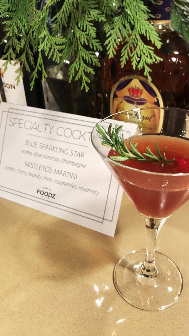 Mistletoe Martini - Bright and cheery, this colorful cocktail features vodka, cherry brandy, lime, raspberries, & a rosemary garnish.from Foodz Catering
