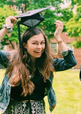Grace placing a graduation cap on her head.