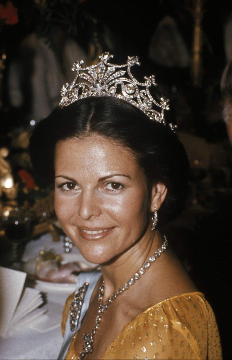 Königin Silvia kann wieder lächeln, nachdem sie heimlich die strammen Nadeln entfernt hatte, mit denen ihr Diadem befestigt wurde. © picture alliance / IBL Schweden