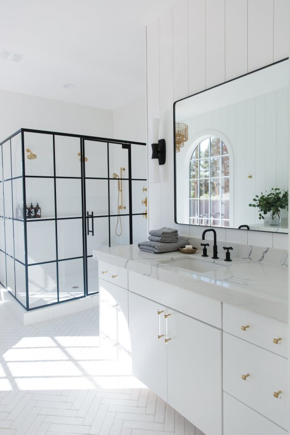Light filled bathroom design with black framed glass shower enclosure, vertical shiplap walls, herringbone tile, white vanity, and black and gold accents - Life Styled
